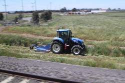 Tractor at work slashing grass beside the RRL tracks at Ravenhall