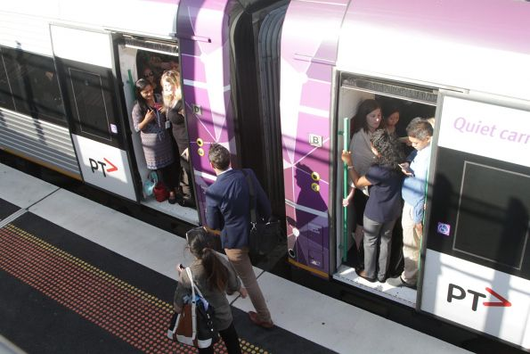 Passengers spilling out of the doors of their overcrowded VLocity train