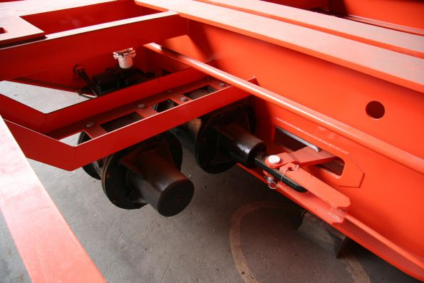 Brake and auxiliary cylinders connected to the brake rigging, beneath a skeletal container wagon
