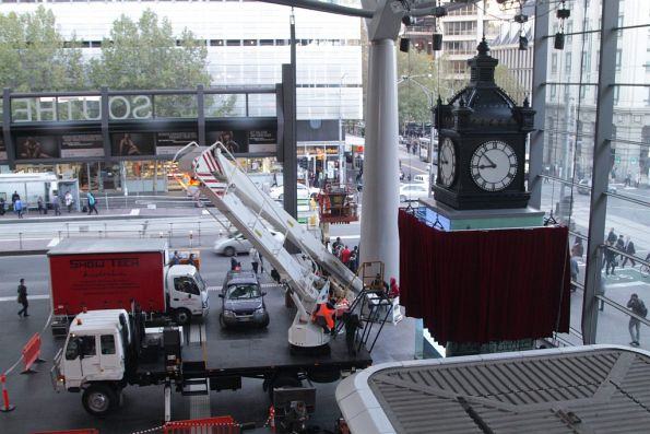 Stage rigging company setting up a big red curtain over the recently installed Water Tower Clock