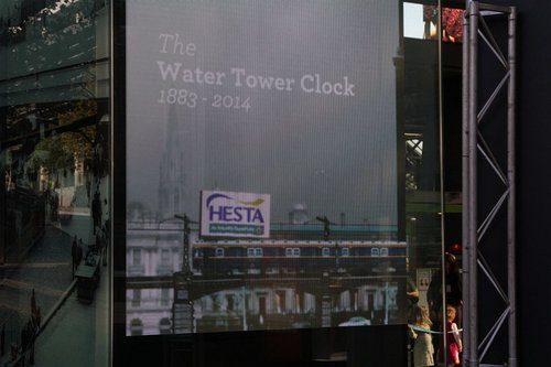 Video wall beneath the Water Tower Clock showing an animated loop of Melbourne trains over the years