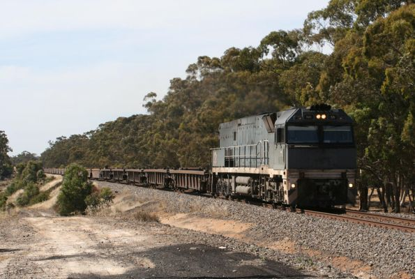 SteelLink liveried NR59 heads a train full of empty well wagons eastbound into Ararat