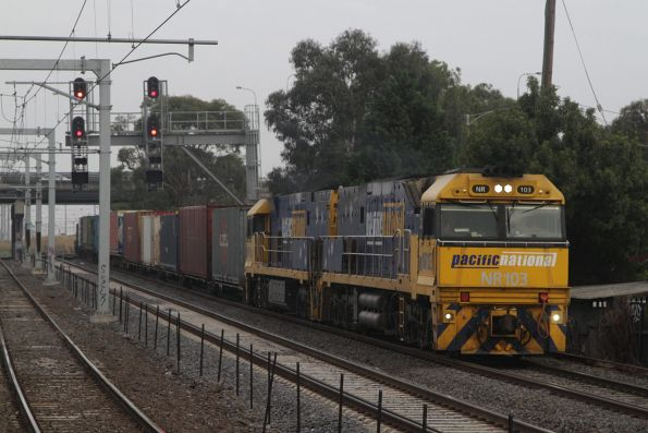 NR103 leads NR117 on AM5 up freight through Middle Footscray