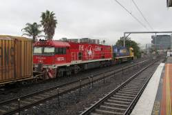 NR112 and Ghan liveried NR74 lead AM5 up freight through Middle Footscray