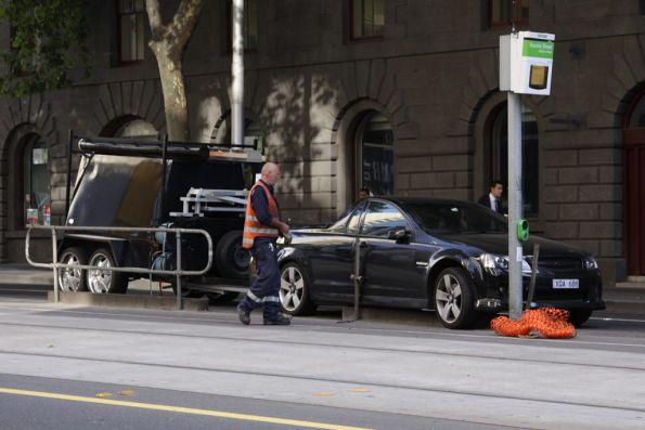 Tradie's ute after mounting the safety zone fence on William Street at Bourke Street