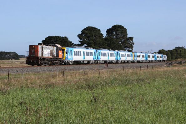 Suburban train rolling through the paddocks