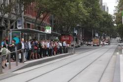 Crowd of passengers waiting at Southern Cross for the first eastbound tram along Bourke Street