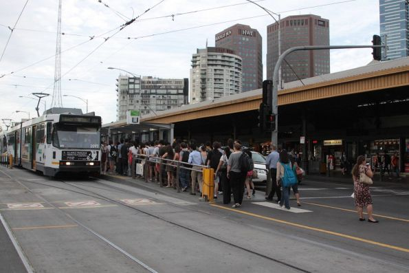 Passengers queue to get access to the Federation Square tram stop in morning peak