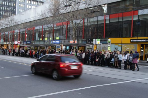 Big crowd of waiting passengers at the corner of Elizabeth and Bourke Streets