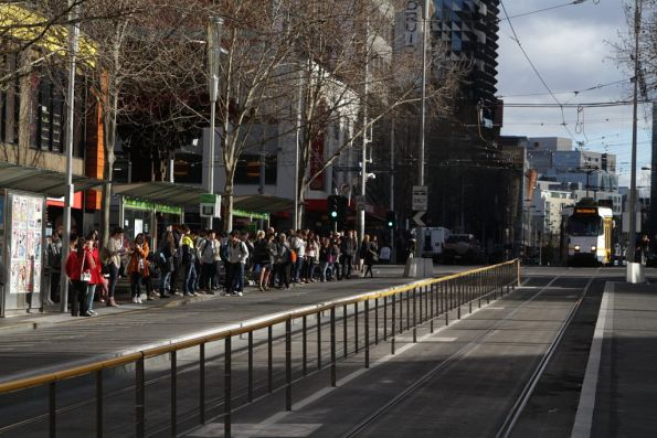 Crowd of passengers waits outside Melbourne Central for the next tram towards Melbourne University
