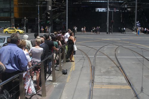 Crowd of exiting tram passengers waiting for the traffic lights at Spencer and Bourke Street