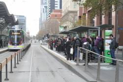 Route 96 passengers fill the southbound tram stop at Spencer and Collins Street