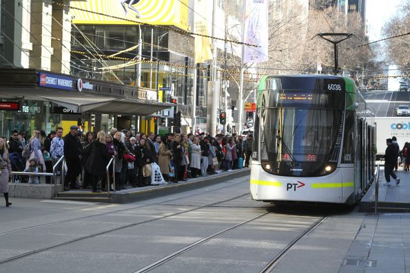 E.6038 passes a packed westbound tram stop at Bourke and Elizabeth Street