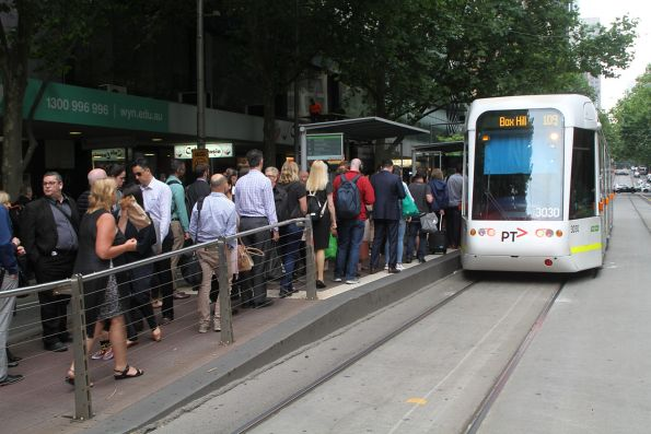 Crowd of intending passengers swarm eastbound route 109 tram C.3030 at Collins and Swanston Street